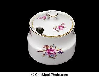 porcelain sugar bowl on black background