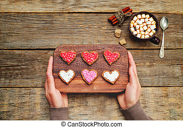 Male hands holding cookies in the forms of heart. toning....