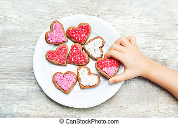 Children's hands holding cookie in the forms of heart....