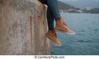 Woman sitting on pier admire picturesque landscape of Montenegro.