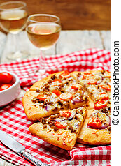 Minced meat tomato red onion pizza on a wood background....