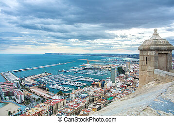 A view from Santa Barbara Castle at the hill in the center of Alicante to a port of the city with a plenty of yachts, to roofs of the buildings and to Mediterranean sea on cloudy day, Alicante, Spain.
