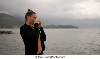 Woman drink coffee standing on lake coast, camera go clockwise.