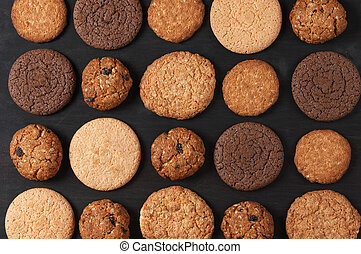 Various cookies on black - Rows of various shortbread and...