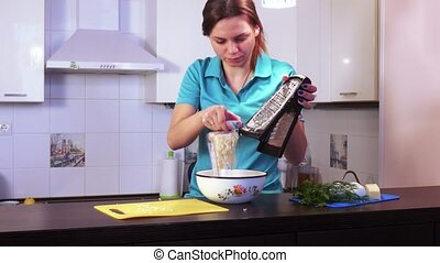Shredding cheese on grater - Brunette girl rubbing cheese on...