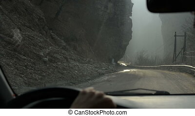 Girl drive along the road in a deep ravine in foggy weather, examining the rocks