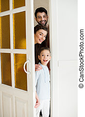 portrait of happy family looking out door at home