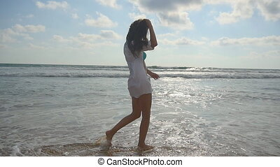 Happy woman walking barefoot in water on the beach near the ocean. Young beautiful girl enjoying life and having fun at seashore. Summer vacation or holiday. Nature landscape at background. Slowmotion