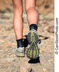 Running in desert - Woman running on trail in desert. Zoom...