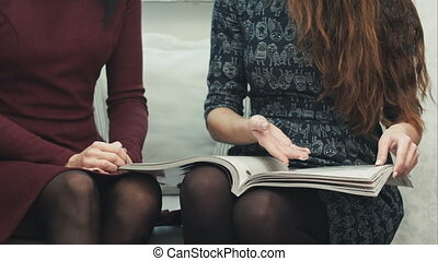 Young female hands flipping through a fashion magazine...