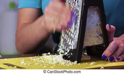 Chopping chicken egg with grater - Brunette girl rubbing...