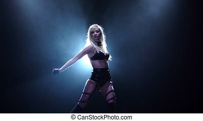Woman in black underclothes dances in black background. Slow...