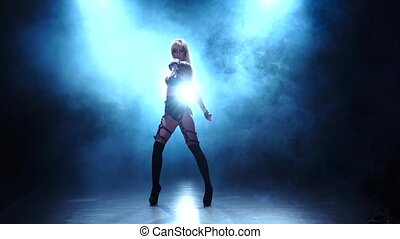 Woman in leather underclothes dances in smoke studio. Slow...