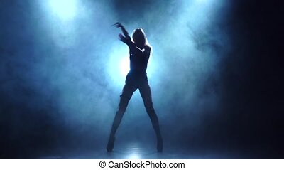 Blonde showgirl in leather lingerie dances, smoky...