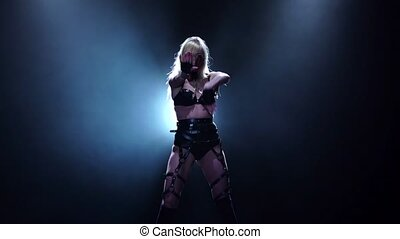 Girl in leather dances in black background. Slow motion -...