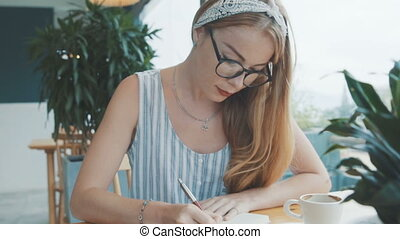 Young beautiful blonde woman daydreaming and writing in her journal, diary. Female write in notebook in cafe.