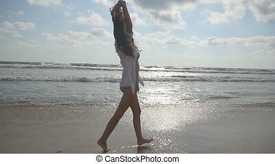 Young beautiful girl enjoying life and having fun at sea shore. Happy woman walking on the beach near the ocean. Summer vacation or holiday. Nature landscape at background. Slow motion