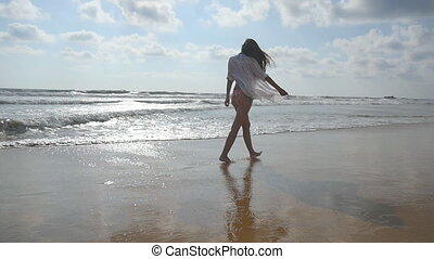 Happy woman in bikini and shirt walking on the beach near the ocean. Young beautiful girl enjoying life and having fun at sea shore. Summer vacation or holiday. Rear back view. Slow motion