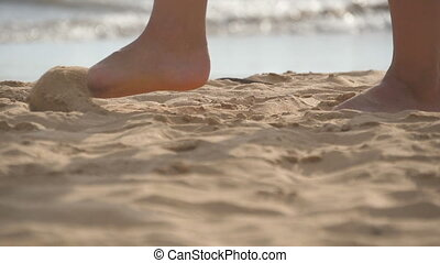 Close up of female feet walking on golden sand at the beach...