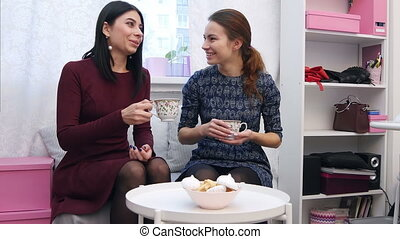 Beautiful young women friends drinking tea in clothes showroom after the shopping