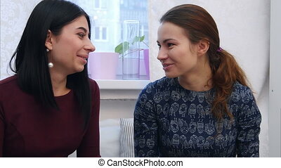 Smiling young women drinking coffee or tea and gossiping....