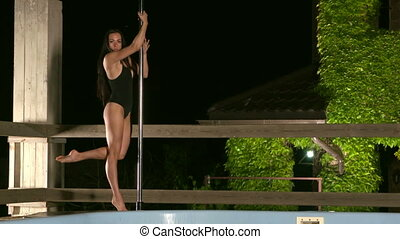 poledancer in bodysuit performs pole dance poses and spins...