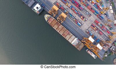 Aerial view of container ships and lifting cranes in the...