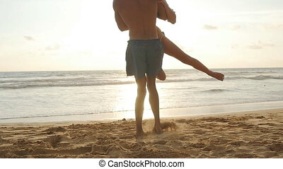 Young couple on the beach, man hug and spin around his woman on sunset. Girl jumps into her boyfriend arms, he whirling her at beautiful seaside. Having fun together at vacation. Slow motion