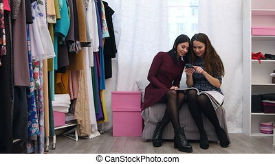 Sales assistant in clothing store helping to chose a customer new dress using smartphone and fashion magazine