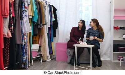 Dressmaker talking about new colletion to a customer, while drinking tea sitting on a sofa in her sewing atelier