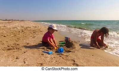 Two Children Building Sand Castle On The Beach - This is a...