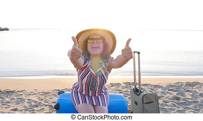 Happy young woman on vacation with a suitcase showing thumbs up