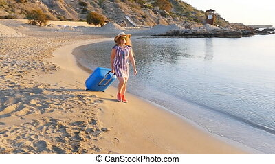 Attractive young woman with suitcase on the beach. Travel...