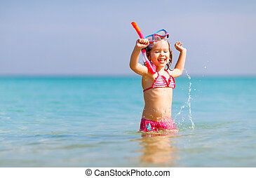 Happy child girl in a mask on the beach