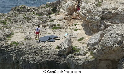 Portable stage pole installation on rocky cliff. Two young...