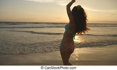 Attractive sexy girl with long hair posing on the ocean shore at sunrise. Beautiful young woman in bikini standing in the sea on sunset. Female on the beach enjoying life during vacation. Slow motion