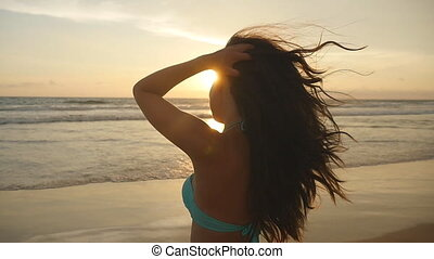 Beautiful young woman in bikini standing in the sea on sunset. Female on the beach enjoying life during vacation. Attractive sexy girl with long hair posing on the ocean shore at sunrise. Slow motion