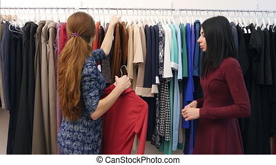 Cheerful saleswoman serving client, help to wear dress near...
