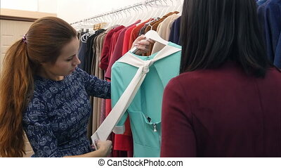 Skillful saleswoman advising client in boutique. Close up....