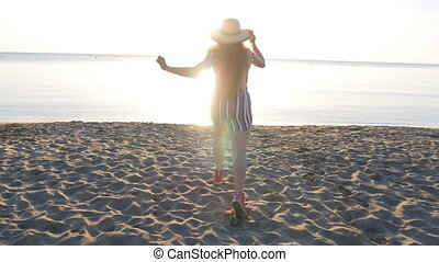 Happy young woman running on the beach - young female...