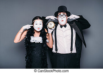 Pantomime actors performing with alarm clock. Comedy artist...