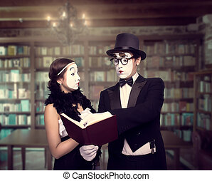 Two pantomime theater performers posing with book. Mime...