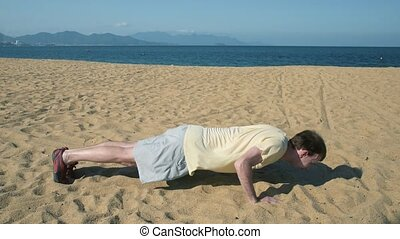 Fit athletic man doing push ups exercise. - Sporty caucasian...