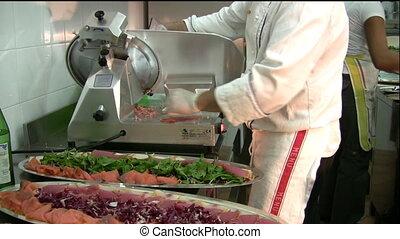 Slicing-machine - A chef using slicing-machine, in an...