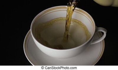 Slow mo. The tea is poured into a cup and saucer on a black...