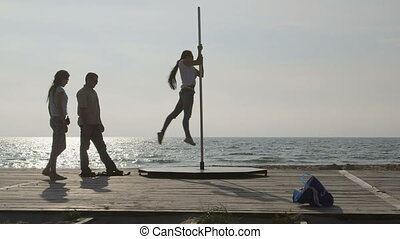 Pole dance fitness exercise on the beach Portable spinning...