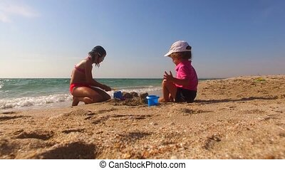 Children Playing With Sand On The Beach - Low angle shot of...