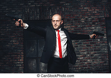 Bald hired killer in red tie aims a pistols - Serious hired...