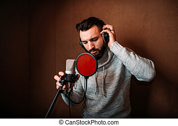 Male singer recording a song in music studio. Vocalist in...