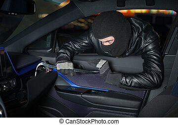 Carjacker unlock glove box with crowbar. Male thief with...
